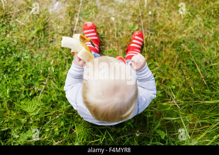 Directly above shot of baby boy holding banana on grassy field - Stock Photo