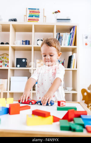 Portrait of little boy playing with toy cars - Stock Photo