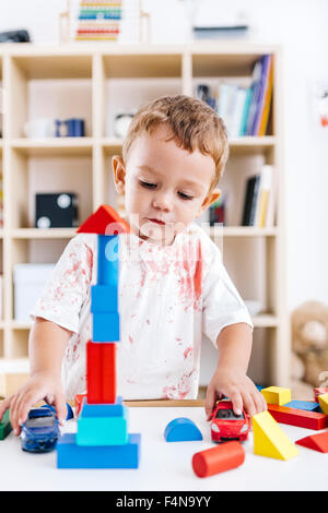 Portrait of excited little boy playing with building bricks and toy cars - Stock Photo