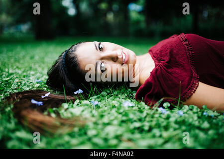 Portrait young woman lying on a meadow - Stock Photo