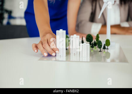 Close-up of hand holding high-rise building model next to wind turbine model on conference table - Stock Photo