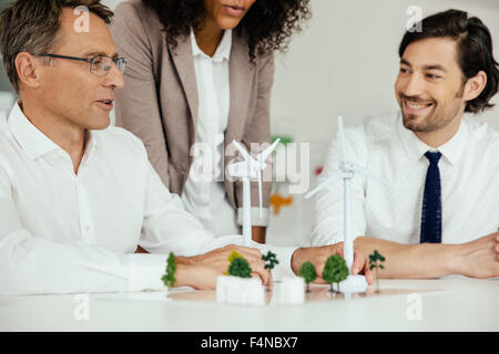 Business people discussing wind turbine model and houses on conference table - Stock Photo