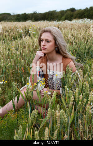 Beautiful girl sitting in a wheat field looking away from the camera - Stock Photo
