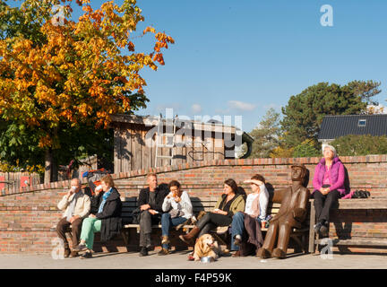 People enjoying the autumn sun on a bench next to the harbour kiosk of Niendorf/Ostsee, a fishing port on the Baltic - Stock Photo
