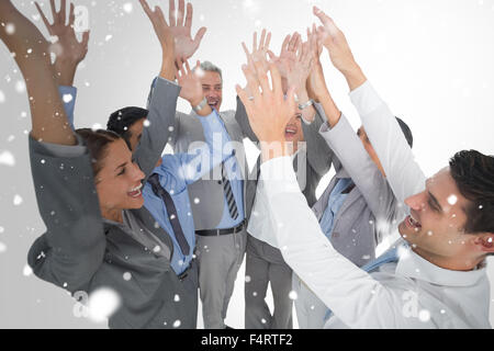 Composite image of business people raising their arms - Stock Photo