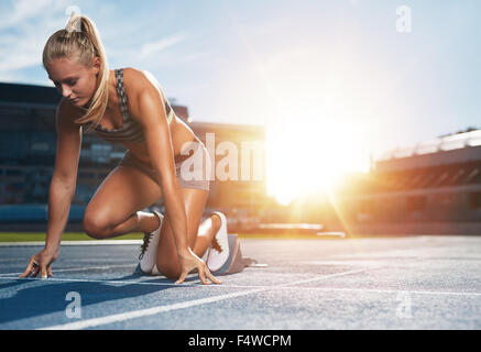 Young woman athlete at starting position ready to start a race. Female sprinter ready for sports exercise on racetrack - Stock Photo