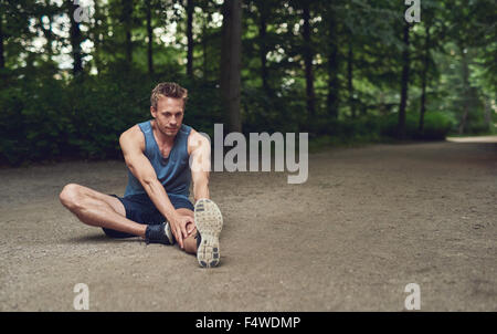 Handsome young male athlete limbering up before training sitting on the ground in a wooded park doing stretching - Stock Photo