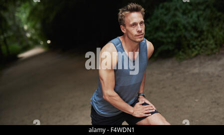 Athletic handsome man warming up before his workout or jog doing stretching exercises outdoors on a track in a wooded - Stock Photo