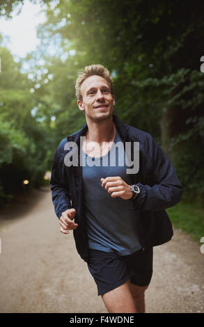 Healthy young man jogging through a park on a sunny morning doing his daily training and workout, close up view - Stock Photo