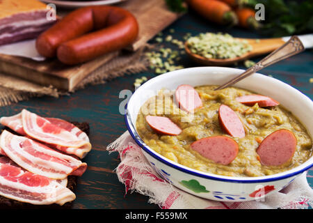 Hearty traditional Dutch pea soup with smoked sausage, rye bread and bacon. Or: 'erwtensoep met rookworst, roggebrood - Stock Photo