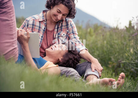 A couple, a woman with an open book looking up at a man smiling at him. - Stock Photo