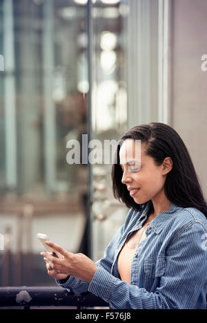 A young woman checking her cell phone on a city street - Stock Photo