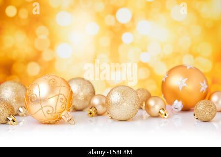 Golden Christmas baubles in front of defocused golden lights. - Stock Photo