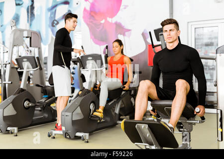 Group of young people working out together in a gym - Stock Photo