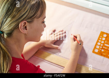 University student of Interior Design doing homeworks, completing housing project for final exam. The girl draws - Stock Photo