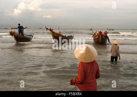 Lady awaiting the landing of the catch, Mui Ne fishing village, Bình Thuận Province, Vietnam - Stock Photo
