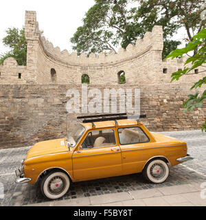 Old car parked on a street in İcheri Sheher, the old town in Baku, the capital of Azerbaijan. - Stock Photo
