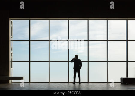 Stylish business man in the background of a large window - Stock Photo