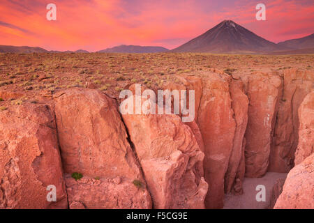 A narrow canyon with a volcano in the distance. Photographed at the foot of Volcan Licancabur in the Atacama Desert, - Stock Photo
