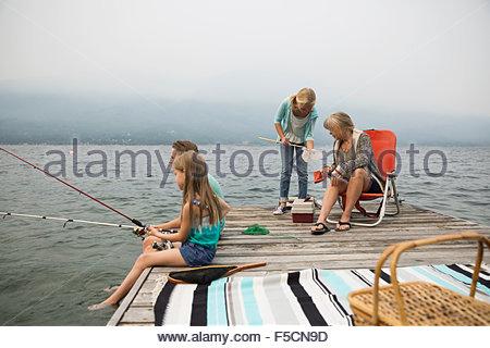 Grandmother and grandchildren fishing on lake dock - Stock Photo