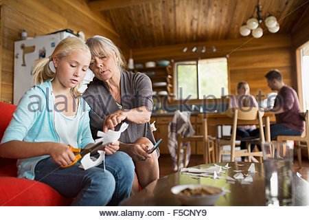 Grandmother and granddaughter cutting paper chain in cabin - Stock Photo