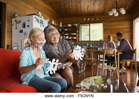 Grandmother and granddaughter making paper chains in cabin - Stock Photo