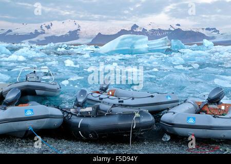 Dinghies, icebergs and snow-covered mountains, Jokulsarlon Glacier Lagoon,  Vatnajokull National Park, Iceland - Stock Photo