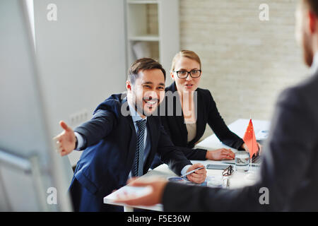 Business people welcoming and registrating foreign partners before conference - Stock Photo