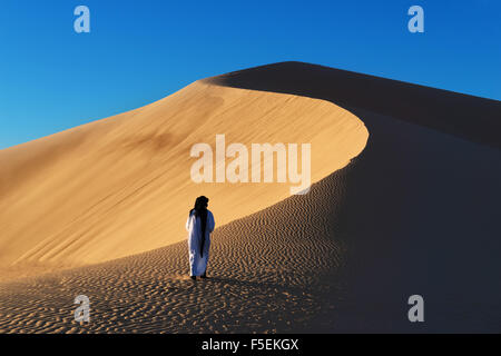 A traditional dressed Moroccan man walks up a sand dune. - Stock Photo