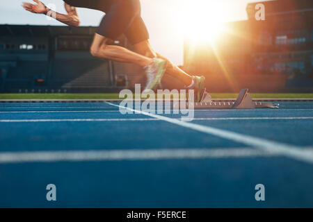 Athlete running on athletic racetrack. Low section shot of male runner starting the sprint from the starting line - Stock Photo