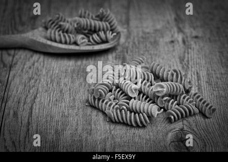 Wholegrain, spelt fusilli pasta with a wooden spoon, black & white. - Stock Photo