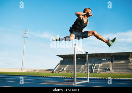 Professional male track and field athlete during obstacle race. Young athlete jumping over a hurdle during training - Stock Photo