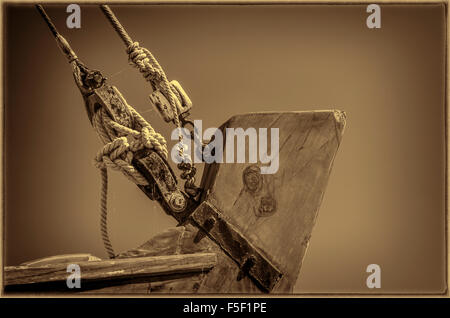 Close up of block and tackle on bow of old wooden boat, sepia finish with vignette and border - Stock Photo