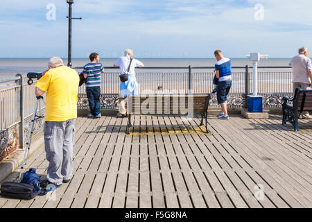 People viewing the sea and the wind farm on the horizon. The seaside from the end of the pier, Skegness, Lincolnshire, - Stock Photo