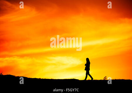 Silhouette of a lonely woman walking at sunset on a hill - Stock Photo