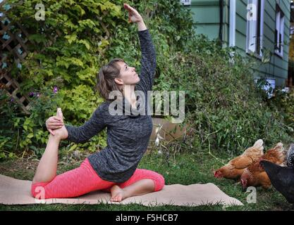 A woman doing yoga outdoors with chickens around. - Stock Photo