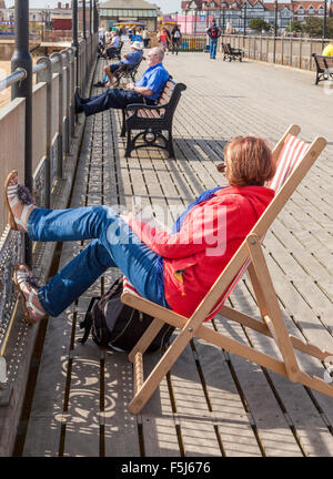 Person sitting on a deck chair and other people sat on benches at Skegness pier, Skegness, Lincolnshire, England, - Stock Photo
