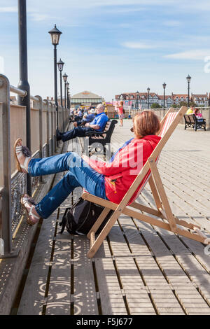 Woman sitting on a deck chair relaxing with her feet up on Skegness pier, Lincolnshire, England, UK - Stock Photo