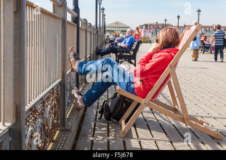 A woman sitting on a deck chair with her feet up along with other people relaxing on a sunny day on Skegness pier, - Stock Photo