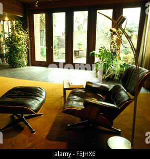 Charles Eames black leather lounge chair and stool in a seventies living room extension - Stock Photo