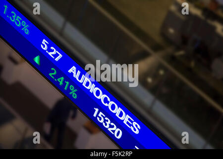 Display stock market charts on blue neon line with blurred office background - Stock Photo
