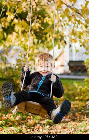 Sweden, Sodermanland, Strangnas, Boy (4-5) playing on swing in garden - Stock Photo