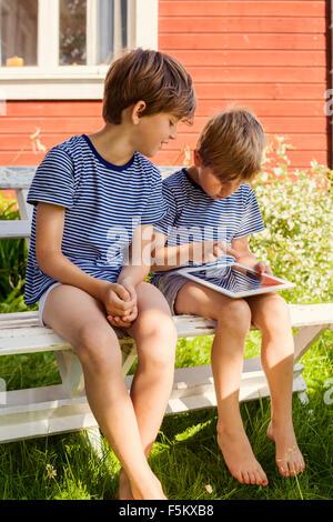 Sweden, Halsingland, Jarvso, Brothers (4-5, 6-7) using digital tablet - Stock Photo