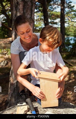 Sweden, Uppland, Runmaro, Barrskar, Mother helping son (6-7) to build birdhouse - Stock Photo