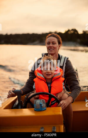 Sweden, Uppland, Runmaro, Barrskar, Portrait of mother and son (4-5) on motorboat - Stock Photo