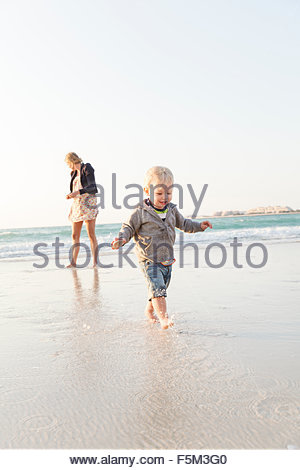 United Arab Emirates, Dubai, Woman with son (12-17 months) on beach - Stock Photo