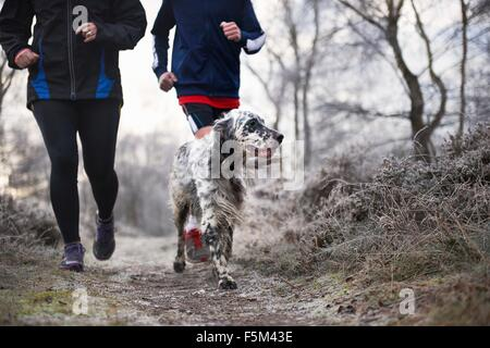 Neck down of mother and son running with dog - Stock Photo