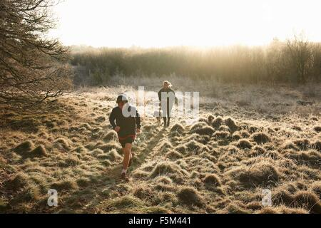High angle front view of mother, son and dog running on grassland - Stock Photo