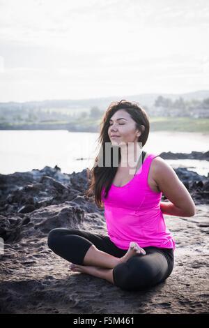 Woman at coast practicing yoga in lotus position, Hawea Point, Maui, Hawaii, USA - Stock Photo