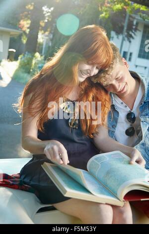 Young couple in vintage convertible reading road atlas - Stock Photo